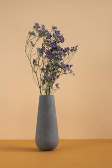Bukiet niebieskich suszonych kwiatów w szarej glinie lub wazonie ceramicznym stojącym na stole jako dekoracja pokoju domowego lub części wnętrza studia