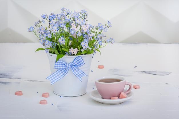 Bukiet niezapominajki w metalowym wiaderku i filiżance herbaty