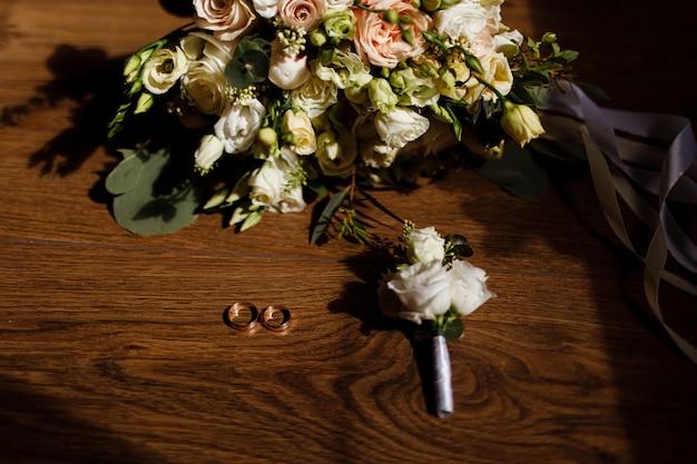 Bukiet panny młodej, boutonniere pana młodego i złote obrączki na drewnianym stole w stylu rustykalnym. akcesoria ślubne.