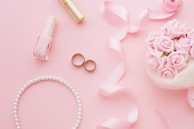 Bukiet panny młodej z różowych róż, obrączek ślubnych, naszyjnika, lakieru do paznokci i różowej wstążki