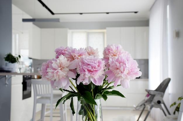 Bukiet pastelowych różowych kwiatów piwonii w rozkwicie z białą kuchnią na tle