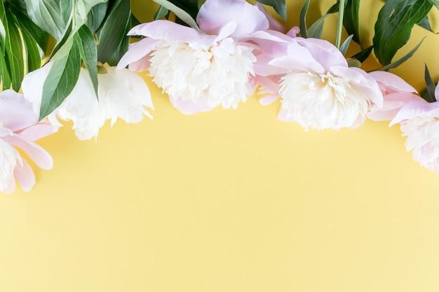 Bukiet pastelowych różowych piwonii na żółto