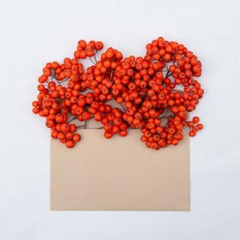 Bukiet pęczków jarzębiny z jasnopomarańczowymi soczystymi jagodami w kopercie z miejscem na kopię