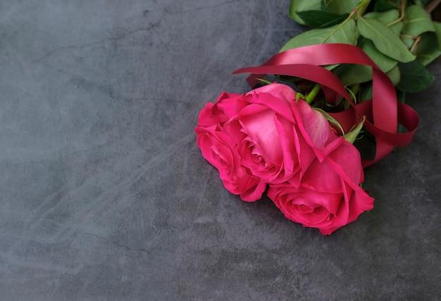 Bukiet pięciu czerwonych róż na szarej powierzchni