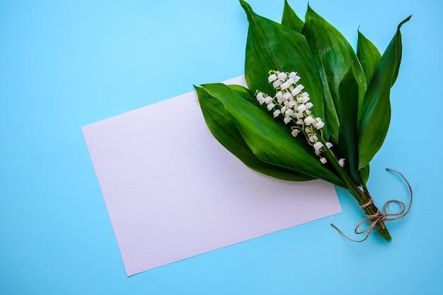 Bukiet pięknych białych konwalii z zielonymi liśćmi i kartka białego papieru do pisania na niebieskiej powierzchni