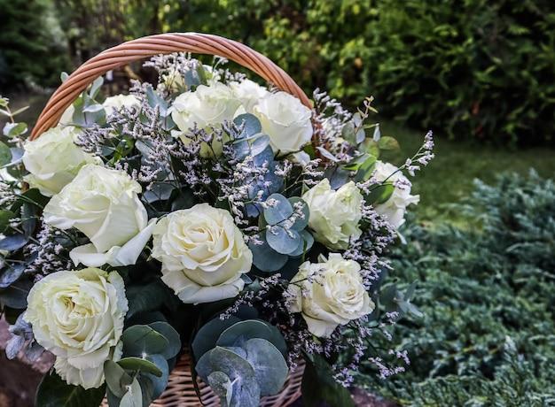 Bukiet pięknych białych róż w wiklinowym koszu na zielonym tle idealny na kartkę z życzeniami