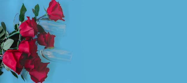 Bukiet pięknych czerwonych róż i dwa kieliszki do szampana leżą na górze na niebieskim tle widok z góry ...
