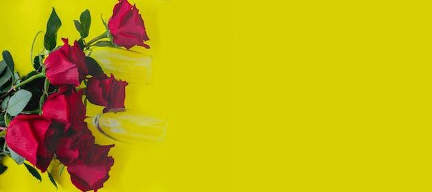 Bukiet pięknych czerwonych róż i dwa kieliszki do szampana leżą z boku na żółtym tle...