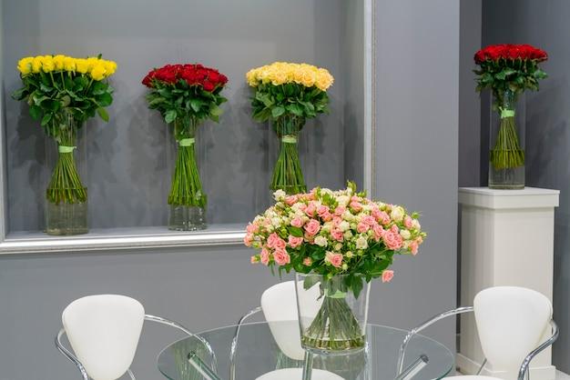 Bukiet pięknych czerwonych róż na stole. kwiatowy uroczysty naturalne tło.