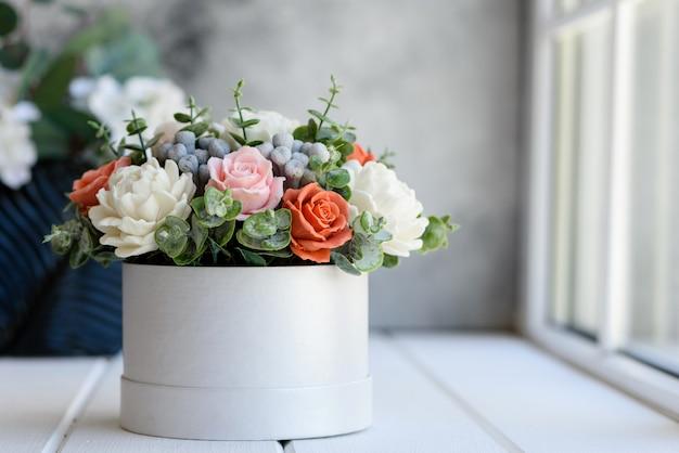 Bukiet pięknych jasnoróżowych kwiatów w prezentowym cylindrycznym pudełku kartonowym