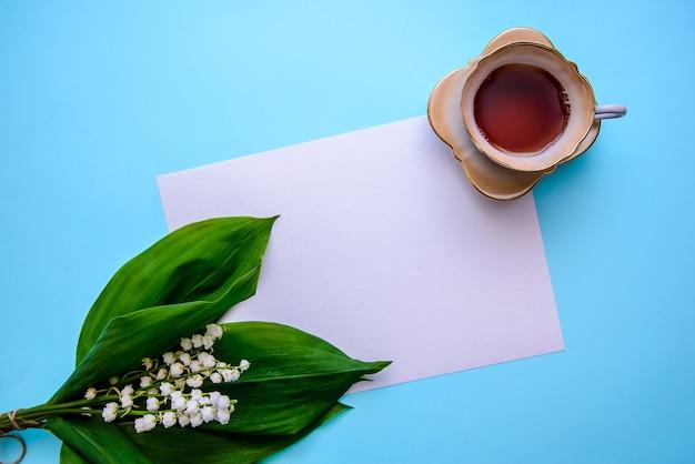 Bukiet pięknych konwalii z zielonymi liśćmi, filiżanką herbaty i białą kartką papieru na niebieskiej powierzchni