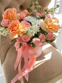 Bukiet pięknych kwiatów brzoskwini w pudełku stoi na krześle w kwiaciarni. kompozycja róż, białej mattioli i chryzantemy. delikatny prezent na wakacje