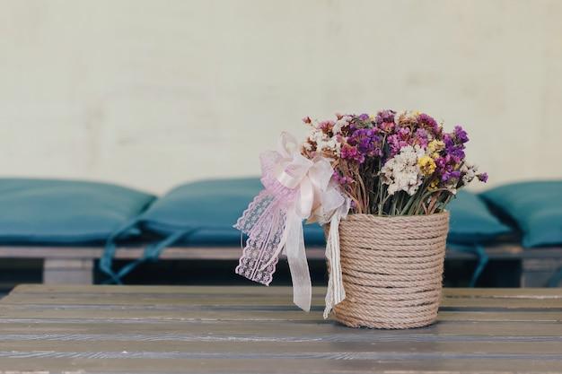 Bukiet pięknych kwiatów w wazonie vintage na drewnianym stole w loftowym wnętrzu