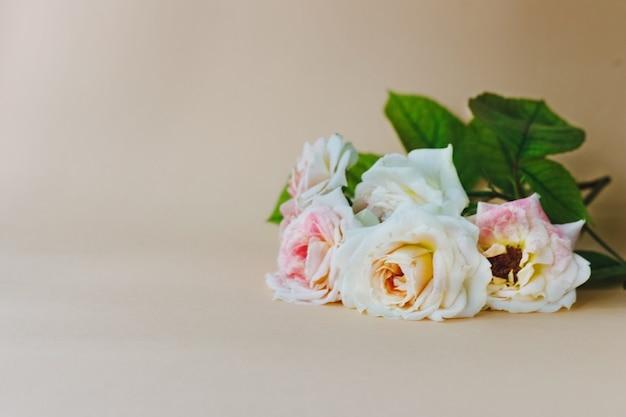 Bukiet pięknych świeżych róż herbacianych na beżowym tle
