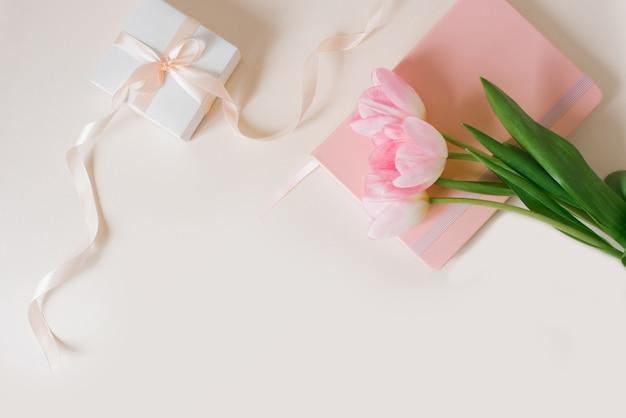 Bukiet pięknych tulipanów i prezent na beżowym tle widok z góry