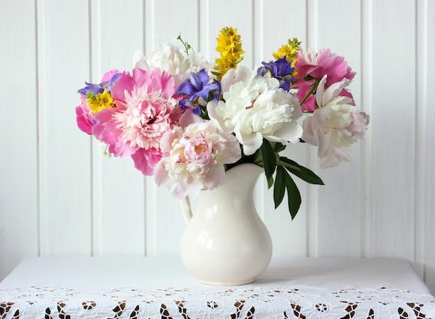 Bukiet piwonii i innych kwiatów w dzbanku.