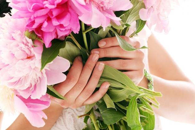 Bukiet piwonii w rękach kobiety