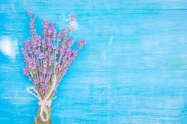Bukiet połączonych kwiatów lawendy na niebieskim drewnianym tle