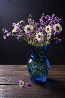 Bukiet polnych kwiatów rumianku, stokrotek i dzwonków na starym drewnianym tle