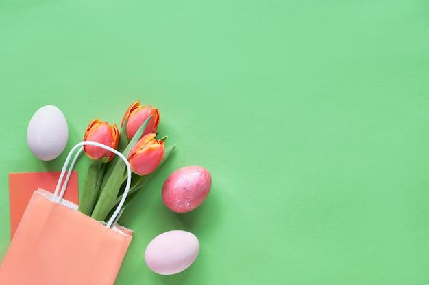 Bukiet pomarańczowych tulipanów w papierowej torbie, ozdobne pisanki i karta podarunkowa, kopia przestrzeń