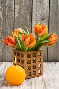 Bukiet pomarańczowych tulipanów, zapalona świeca