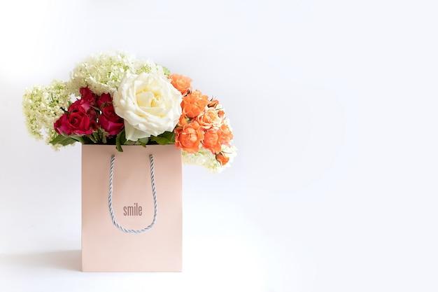 Bukiet prezentowy z wiosennych kwiatów w papierowej torbie prezentowej