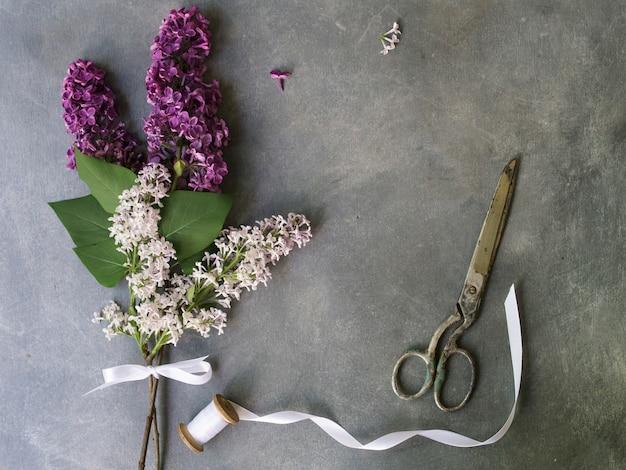 Bukiet purpurowi bzy kwitnie na szarym tle. rocznika kwiecisty tło. skopiuj miejsce