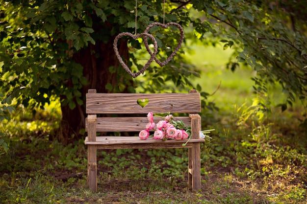 Bukiet ranunculus kwitnie na starej drewnianej ławce na lato naturze