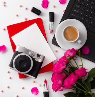Bukiet róż, filiżanka kawy, laptop, kamera, notepad i pomadka na białym stole.