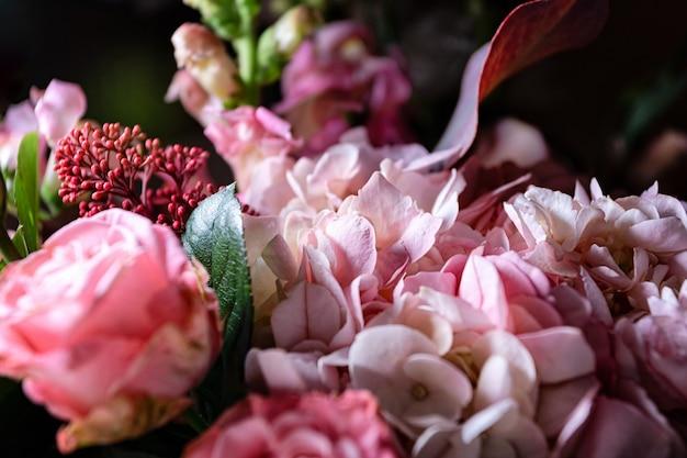 Bukiet róż i kwiatów ogrodowych zbliżenie na czarnym tle z płytką głębią pola i nieb...