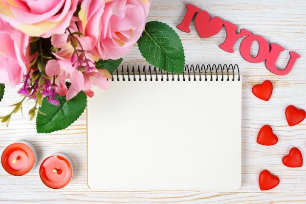 Bukiet róż i walentynkowe serca z papierowym notatnikiem i słowami kocham cię na białym tle drewnianych. widok z góry, płaski układ z miejscem na kopię