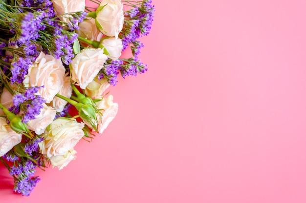 Bukiet róż kremowych i jasne fioletowe kwiaty w pełnym rozkwicie na różowym tle z miejscem na tekst.