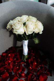 Bukiet róż ślubnych stoi na krześle, a wokół są rozrzucone płatki róż