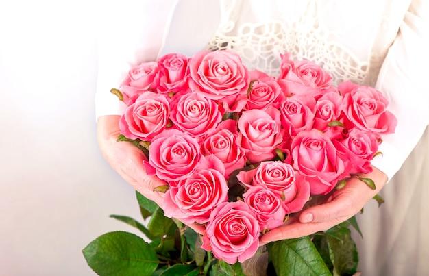 Bukiet róż w kształcie serca w rękach kobiet