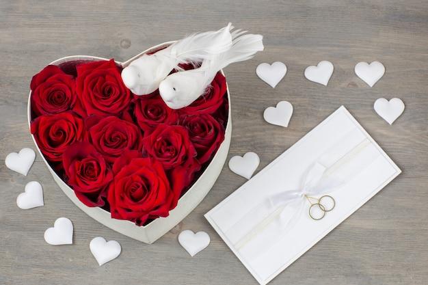 Bukiet róż w pudełku w kształcie serca, kartkę z życzeniami, białe satynowe serca i dwa białe gołębie