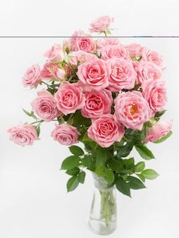 Bukiet róż w szklanym wazonie na białym tle