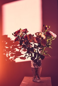 Bukiet róż w szklanym wazonie stoi na drewnianym stołku na tle ściany w promieniach słońca.