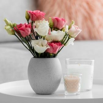 Bukiet róż w wazonie obok świec