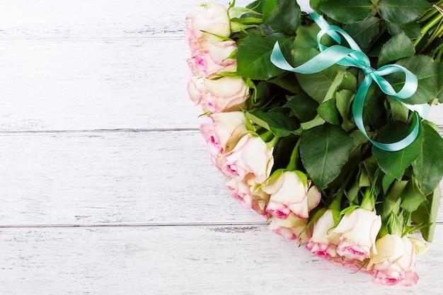 Bukiet róż z niebieską wstążką na vintage tle drewnianych