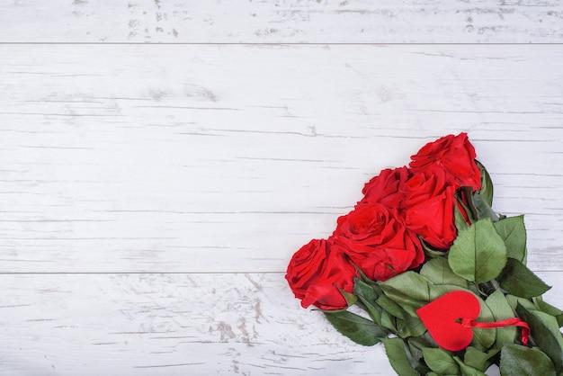 Bukiet róż z ozdobnym sercem i wstążką na białym tle drewnianych.