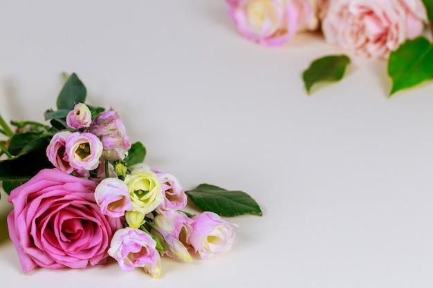Bukiet róż z zielonymi liśćmi na białym tle.