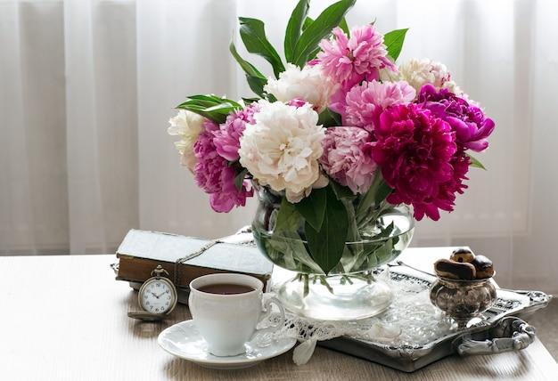 Bukiet różnokolorowych piwonii, eklery w wazonie, filiżanka herbaty, książka i zegarek kieszonkowy
