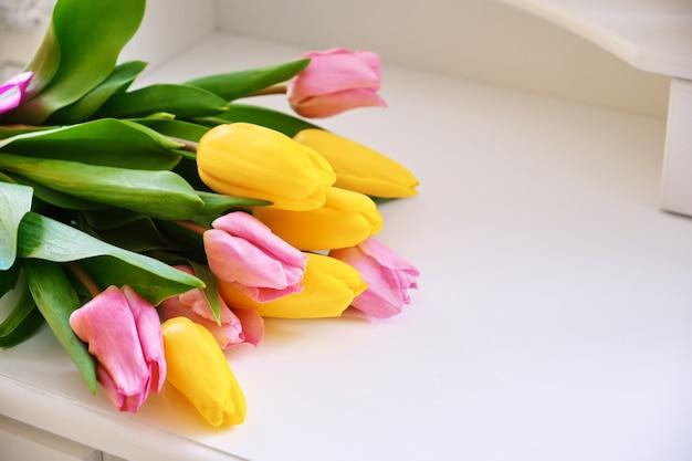 Bukiet różnokolorowych tulipanów na białym stole w jasnym pokoju