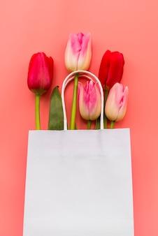 Bukiet różnych tulipanów w papierowej torbie