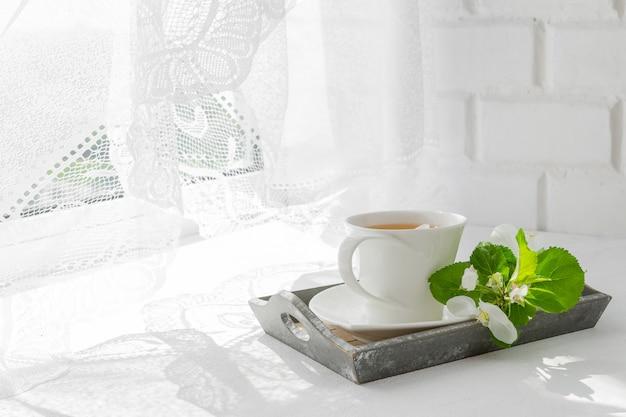 Bukiet różowe kwiaty (róże) i biały serwis na parapecie.