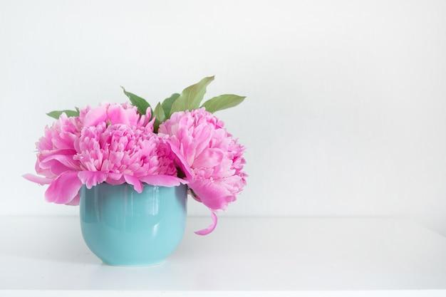 Bukiet różowej piwonii w niebieskim wazonie na białym tle.