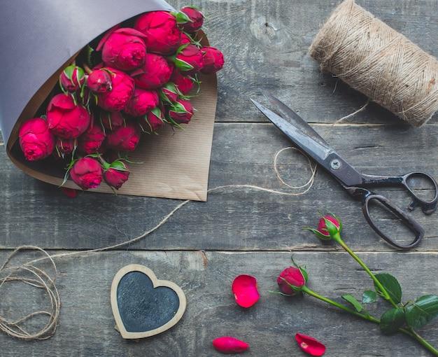 Bukiet różowej róży zawinięty w papier.