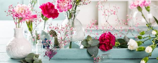 Bukiet różowy goździk na lekkim turkusowym drewnianym tle