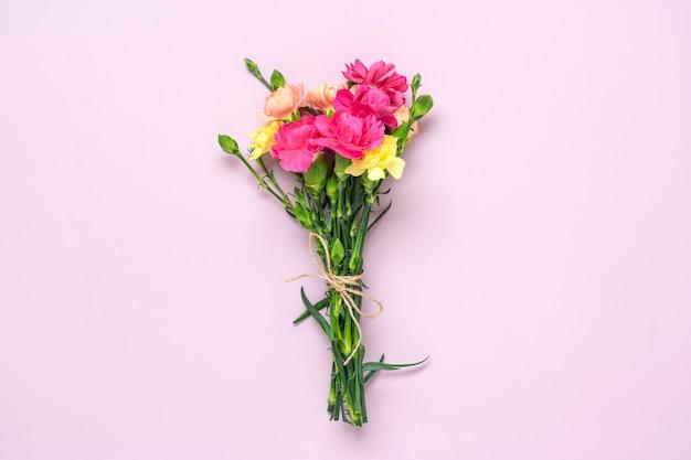 Bukiet różowy kwiat goździka na różowym tle. widok z góry