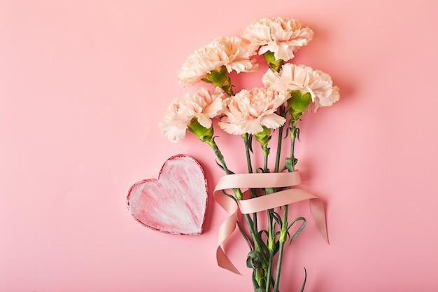 Bukiet różowych goździków i ozdobne serce na różowym tle stołu